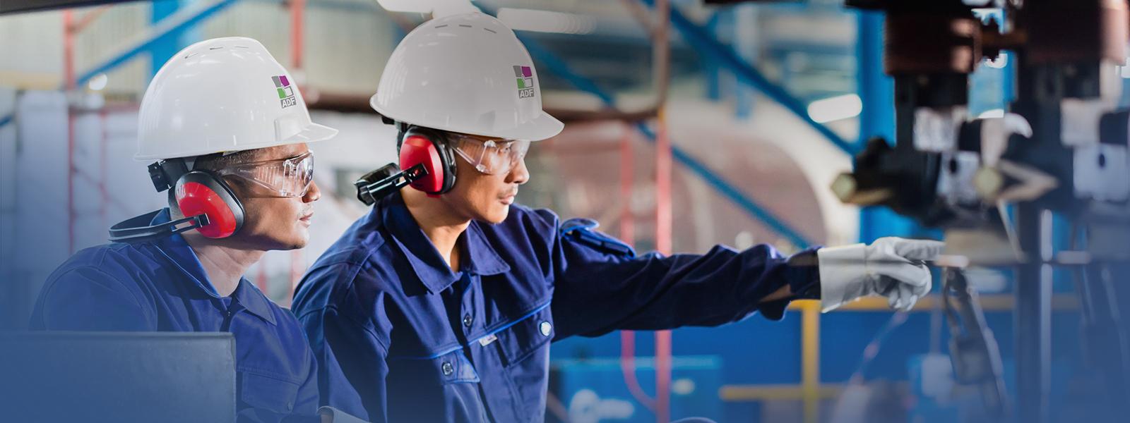 Deze afbeelding toont twee techniekers, in veiligheidskledij, oorbeschermers, een helm en veiligheidsbril die met elkaar praten over het productieproces waar ze aan meewerken.